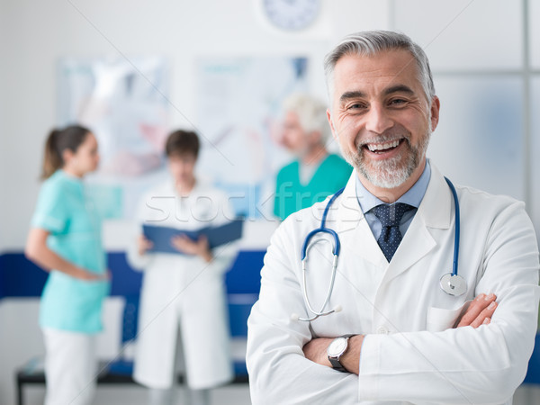 Orvos pózol kórház mosolyog keresztbe tett kar orvosi Stock fotó © stokkete
