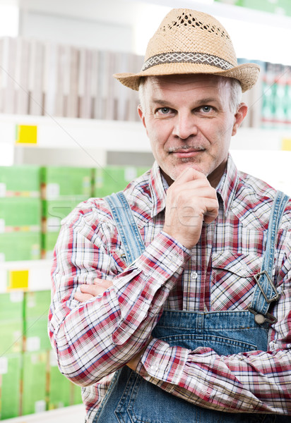 Farmer at supermarket with hand on chin Stock photo © stokkete