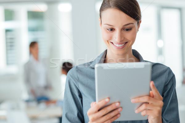 Mujer de negocios pantalla táctil tableta sonriendo pie oficina Foto stock © stokkete