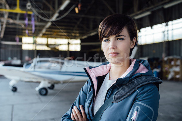 Confident female pilot posing in the hangar Stock photo © stokkete
