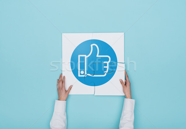 Woman completing a puzzle with thumbs up icon Stock photo © stokkete