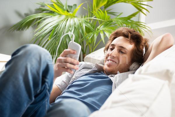 Foto stock: Tipo · auriculares · sofá · sonriendo · joven