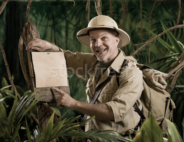 Cheerful explorer pointing to a sign Stock photo © stokkete