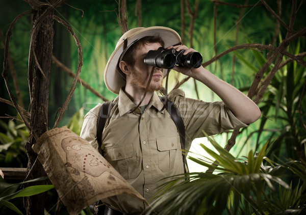 Explorer in the jungle with binoculars Stock photo © stokkete