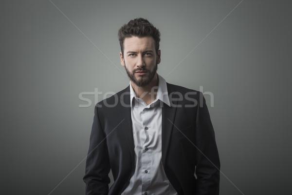 Vonzó fiatal üzletember pózol szürke üzletember Stock fotó © stokkete