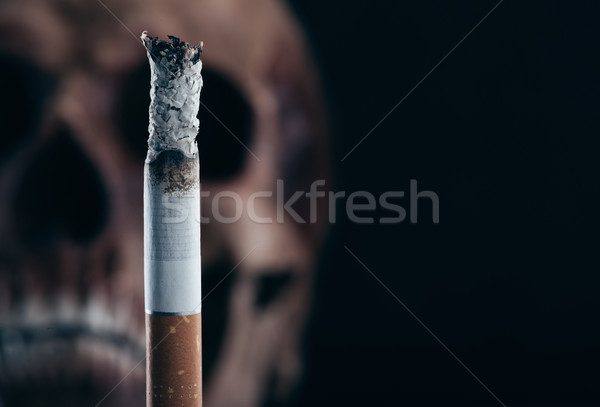 Stock photo: Burning cigarette with skull