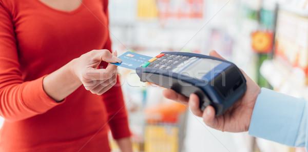 Nő pénztár áruház hitelkártya vásárlás kiskereskedelem Stock fotó © stokkete