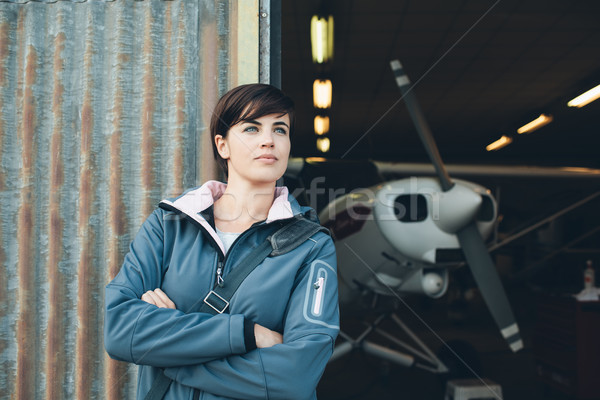 Smiling woman leaning against the hangar walls Stock photo © stokkete