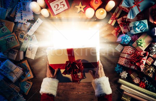Stock photo: Santa opening a gift box
