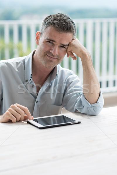 Relaxante terraço sorridente homem sessão tabela Foto stock © stokkete