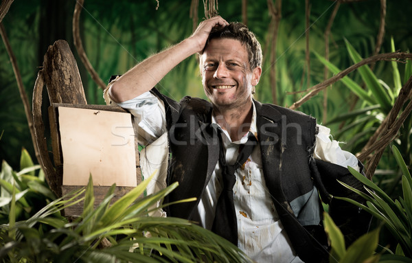 Survivor businessman leaning to a sign in the jungle Stock photo © stokkete