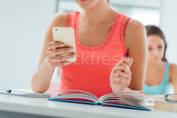 Teenager using mobile in the classroom Stock photo © stokkete