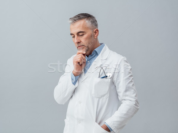 Doctor thinking with hand on chin Stock photo © stokkete