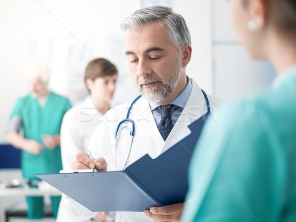 Stock photo: Doctor examining a patient's medical records