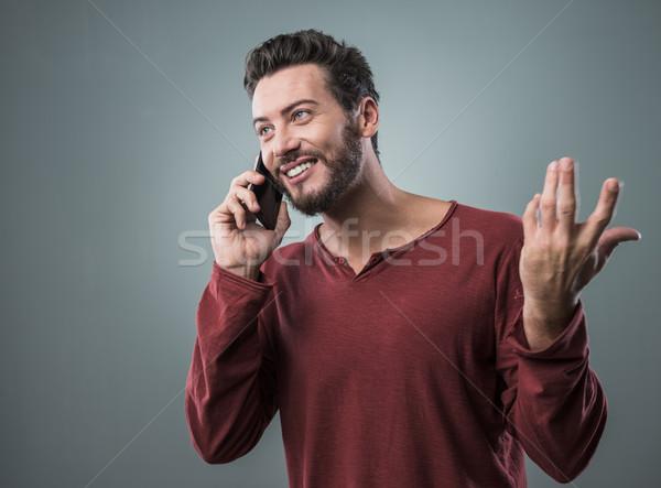 Fiatalember telefonbeszélgetés fiatal mosolyog férfi gesztikulál Stock fotó © stokkete