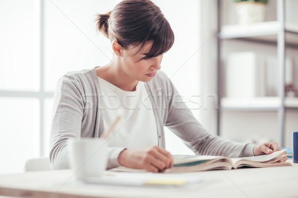 Fiatal nő olvas könyv otthon ül asztal Stock fotó © stokkete