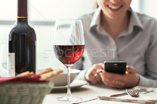 Woman using a smartphone at the restaurant Stock photo © stokkete