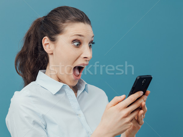 Shocked woman using a smartphone and connecting Stock photo © stokkete