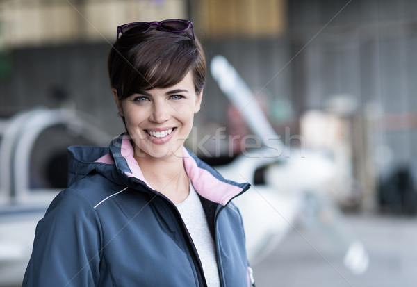 Smiling female pilot posing in the hangar Stock photo © stokkete