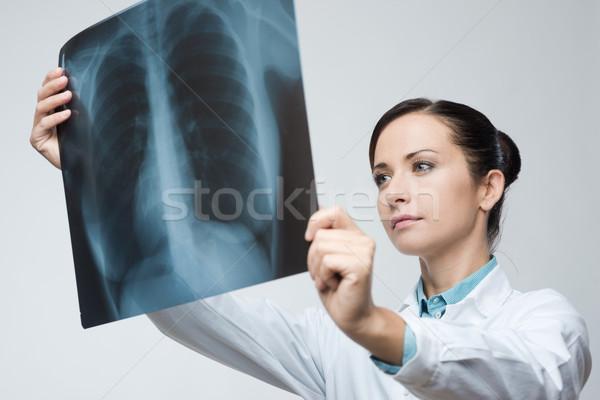 Female doctor examining x-ray image Stock photo © stokkete