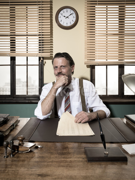Confident businessman working at desk with hand on chin Stock photo © stokkete