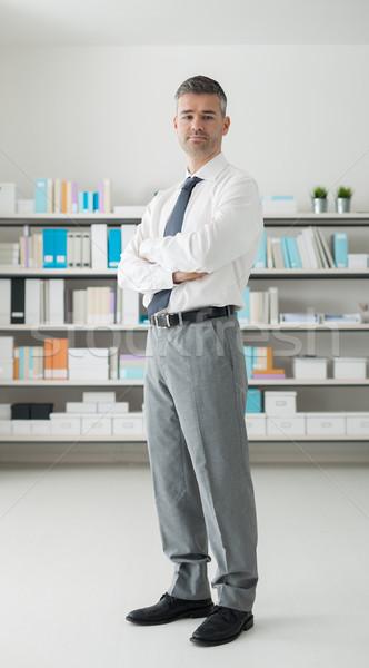 Empresario oficina pie mirando cámara los brazos cruzados Foto stock © stokkete