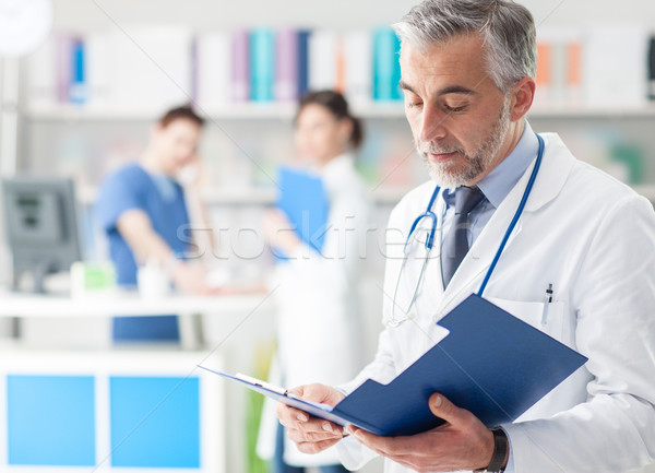 Confident doctor checking medical records Stock photo © stokkete
