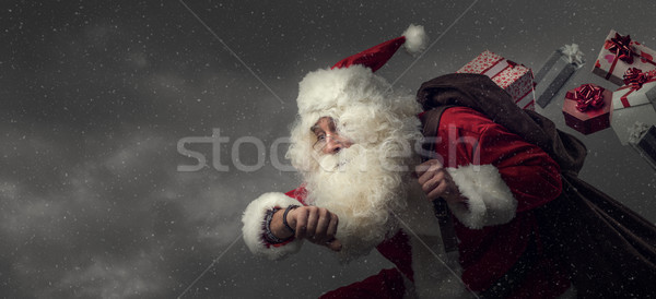 Santa Claus running and delivering gifts Stock photo © stokkete