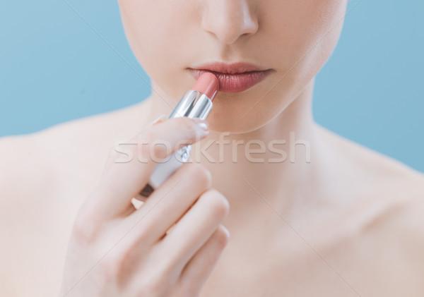 Woman applying lipstick Stock photo © stokkete