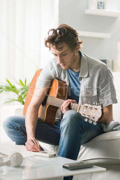 Chanson jeune homme jouer guitare séance canapé Photo stock © stokkete