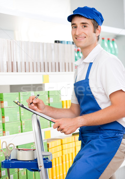 Sales clerk at work on a ladder Stock photo © stokkete