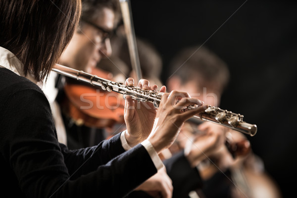 Female flutist with orchestra on stage Stock photo © stokkete