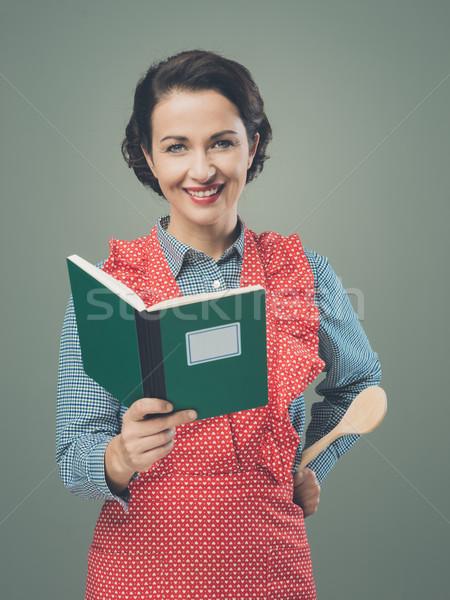 Mujer sonriente delantal libro de cocina sonriendo retro mujer Foto stock © stokkete
