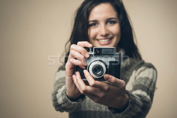 Fiatal nő régi fényképezőgép fiatal vonzó nő mosolyog tart Stock fotó © stokkete
