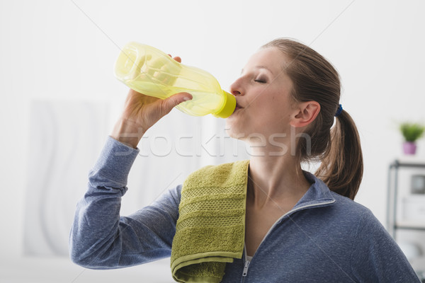 Sporty woman drinking water Stock photo © stokkete
