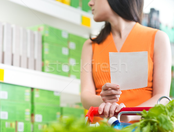 Woman at supermarket with shopping list Stock photo © stokkete