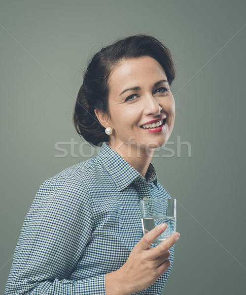 Smiling woman drinking a glass of water Stock photo © stokkete