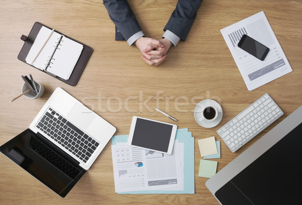Confident businessman with hands clasped Stock photo © stokkete