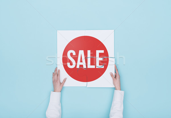 Woman completing a puzzle with a sale badge Stock photo © stokkete