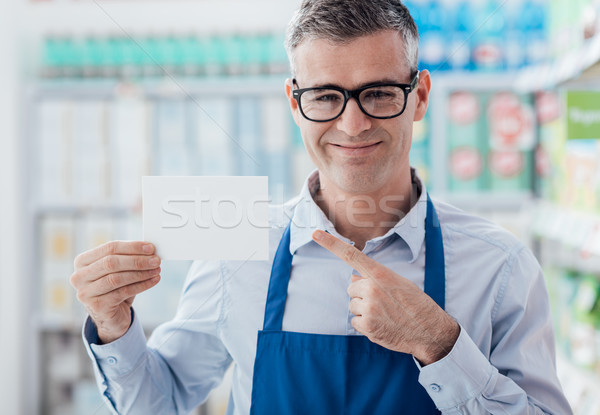Supermarket worker holding a blank card Stock photo © stokkete