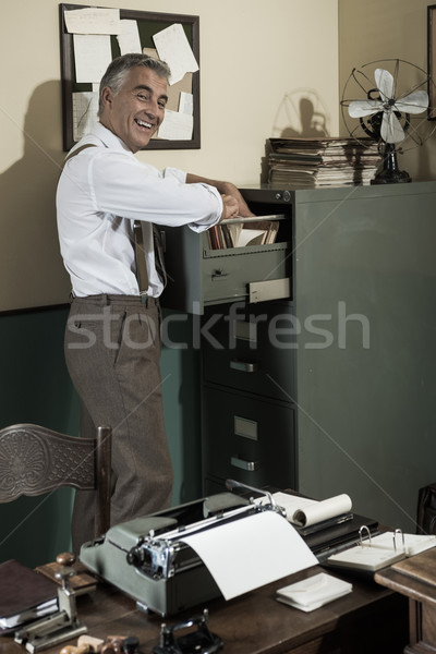 Smiling office worker searching for a file. Stock photo © stokkete