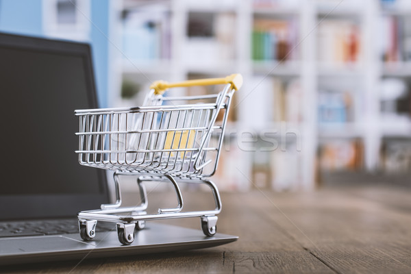 Miniature shopping cart and laptop on a desk Stock photo © stokkete