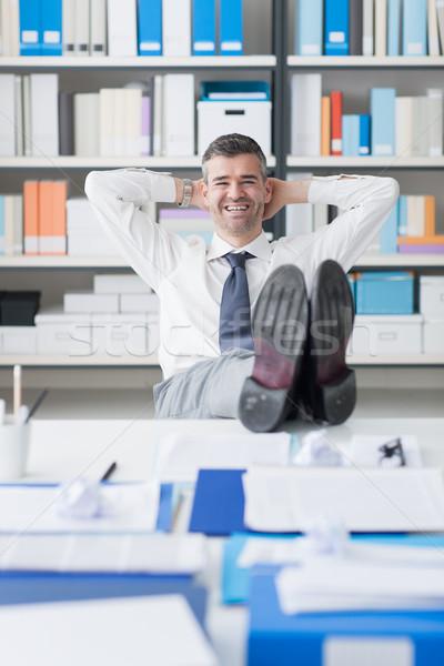 Pigro imprenditore ufficio sorridere rilassante piedi Foto d'archivio © stokkete