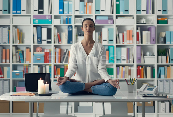 Woman practicing meditation on a desk Stock photo © stokkete