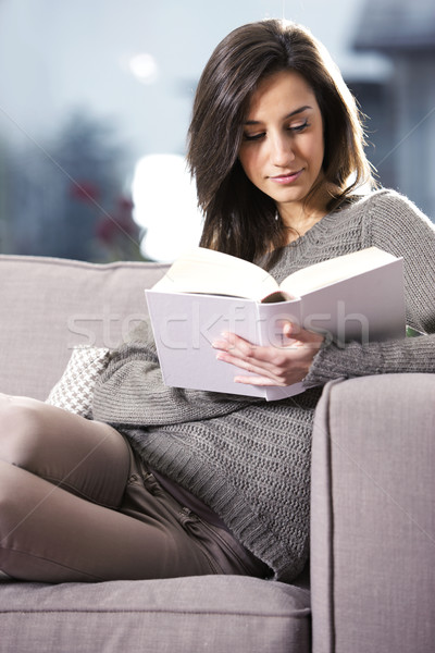 Portrait of a  young woman lying on couch with book Stock photo © stokkete