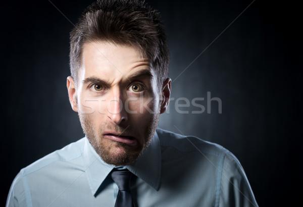 Kétségbeesett üzletember fiatal kiemelt szemöldök szürke Stock fotó © stokkete