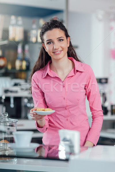 Fiatal barista adag sütik mosolyog mögött Stock fotó © stokkete