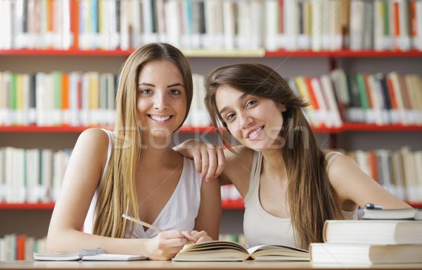 Сток-фото: счастливым · библиотека · два · женщины · студентов · глядя