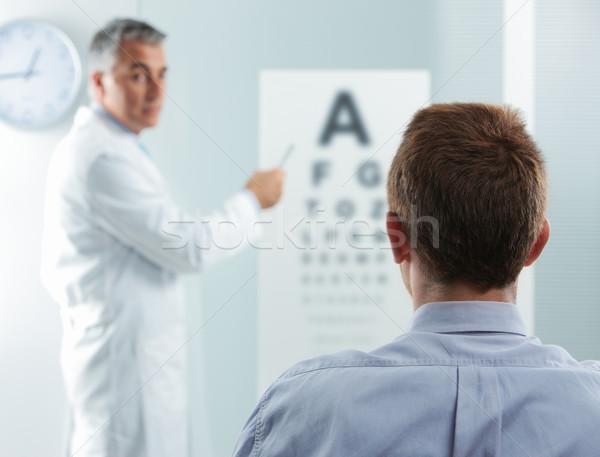Examen de la vue optométriste patient médecin pointant oeil Photo stock © stokkete