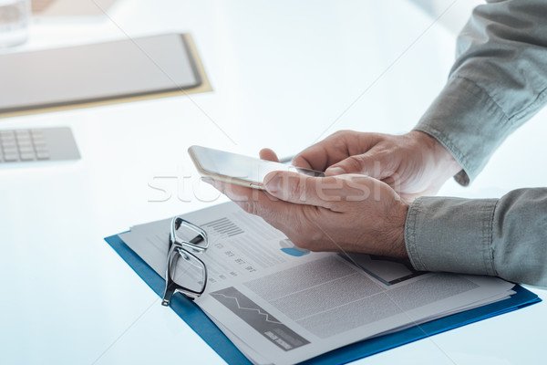Businessman using a smart phone Stock photo © stokkete
